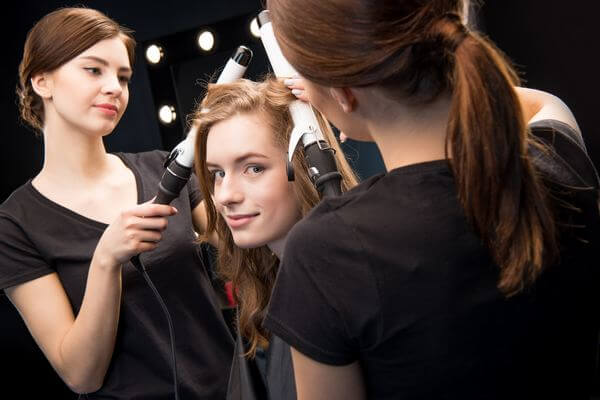 hairstylists curling hair with curling iron
