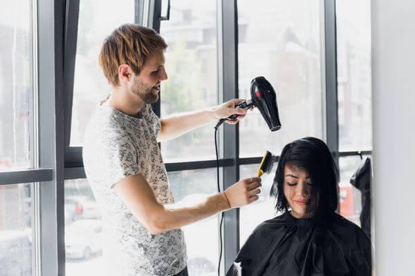 woman getting her hair dressed in hair salon